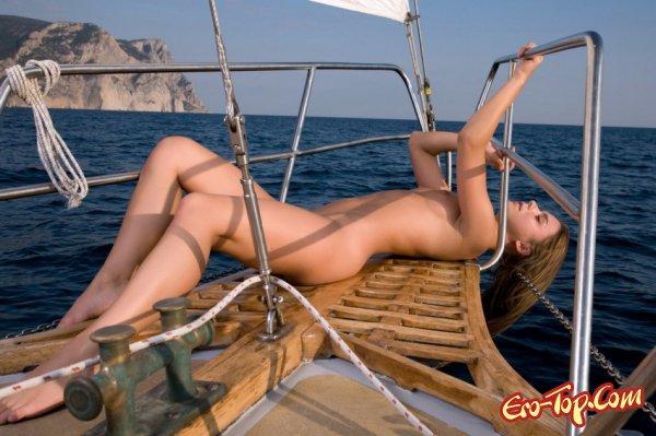 Голая девушка под парусом на яхте