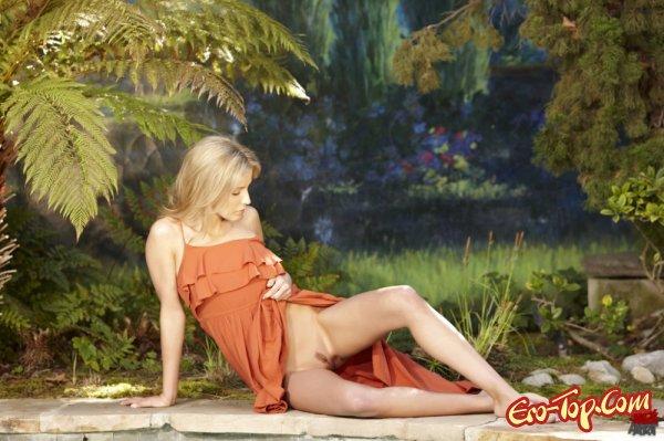 Красивая блондинка задрала подол длинного платья