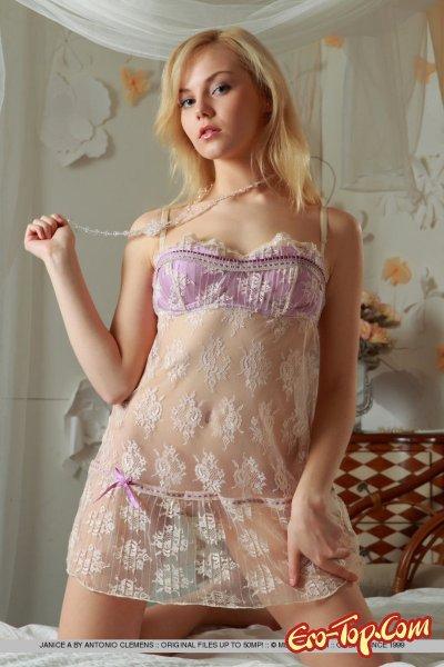 Молодая голая блондинка в большой постели.