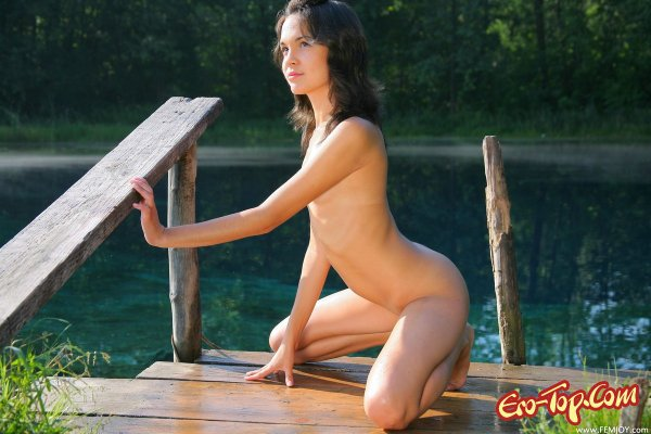 Молодая голая девушка на причале.