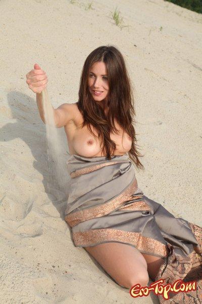 Голая девушка на песке. Смотреть фото.