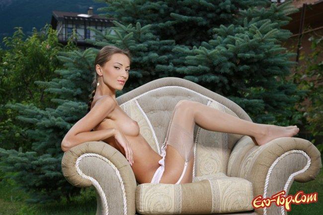 Красивая голая девушка в саду на кресле. Фото.