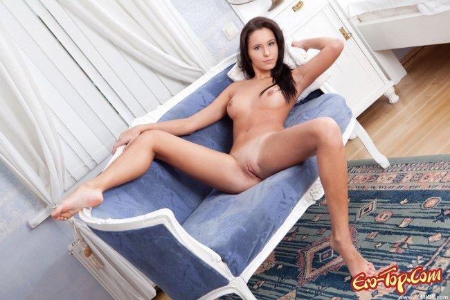 Голая красавица брюнетка на диванчике. Фото эротика.