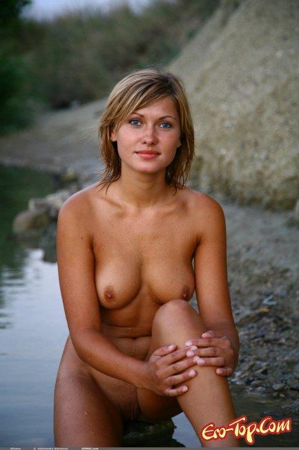Голая девушка купается в речке. Фото эротика.